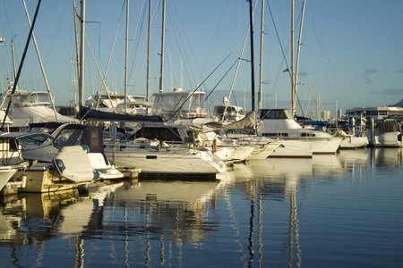 Boats and yachts lined up at the marina in the early morning golden light.