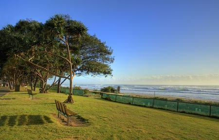 Lonley seats on the beach foreshore with trees in the early morning sun. Stock Photo - 4590525