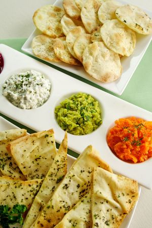 Assorted dips of carrot, cottage cheese and herbs, pea and basil with pita crisps.