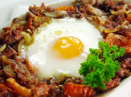 flavorful: Baked corned beef hash with egg, tomato and onion with parsley. Stock Photo