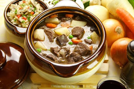 Table setting of freshly baked beef stew with savory rice and seasonal vegetables and herbs. Stock Photo