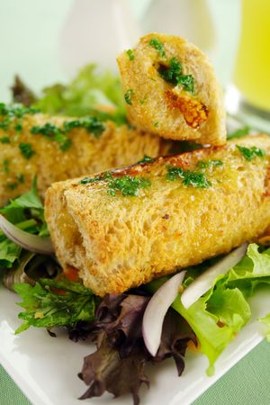 flavorful: Vegetarian baked corn rolls dripping with parsley butter on a bed of mixed lettuce. Stock Photo