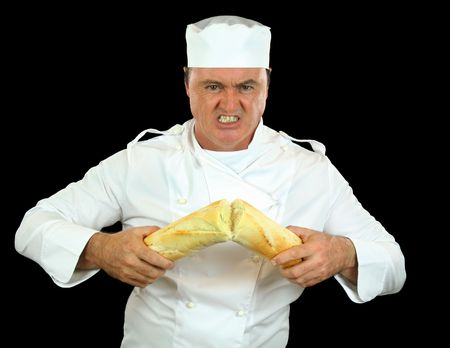 seething: Strongman chef breaks a bread roll with his bare hands. Stock Photo