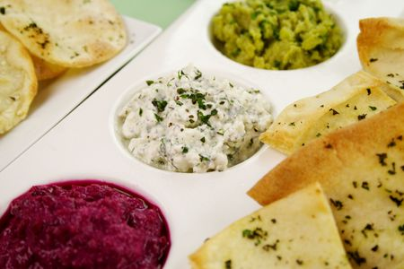 Assorted dips of cottage cheese and herbs, pea and basil with pita crisps. photo
