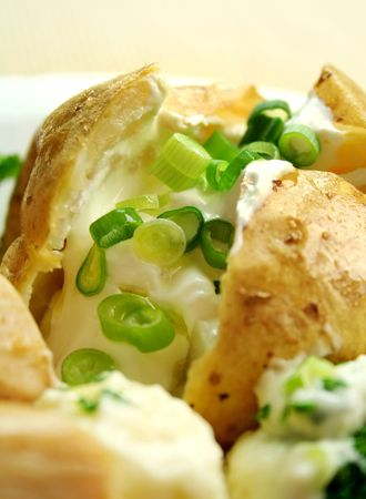 Delicious baked potato with sour cream and diced shallots.