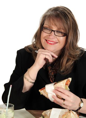 Middle aged businesswoman eats lunch while still working at her desk. photo