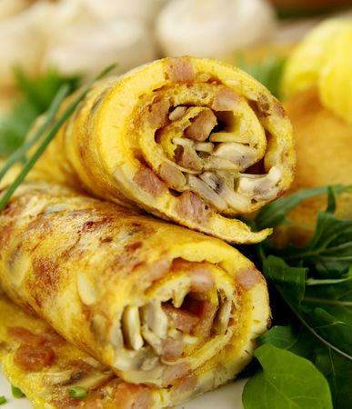 omelette: Delicious rolled mushroom and bacon omelette freshly prepared and ready to serve. Stock Photo