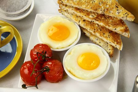 Delicious poached eggs and grilled tomatoes with toast. Stock Photo