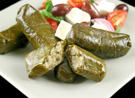 Greek dolmades wrapped with vine leaves and rice with salad. Stock Photo