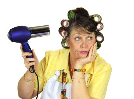 dreary: Totally bored frumpy housewife with hair rollers dries her hair. Stock Photo