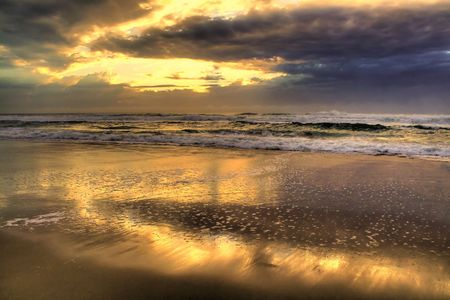 Early morning sun breaks through reflecting on the golden beach. Stock Photo