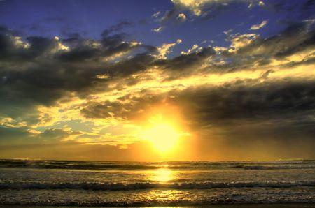 broken through: Sun broken through clouds and blazing over the ocean.