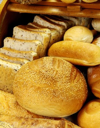 unsliced: Cob bread loaf amongst a selection of different breads. Stock Photo