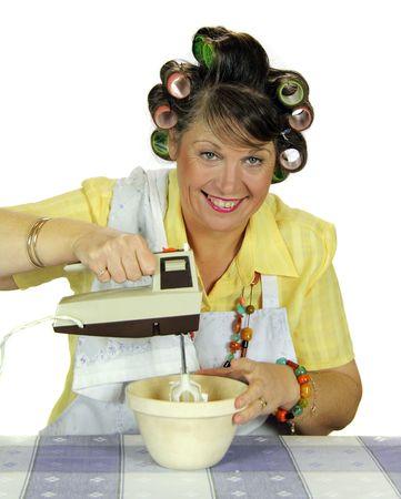 hiebe: Mittleren Alters Frumpy Hausfrau gegen Eier mit einem elektrischen Mixer. Lizenzfreie Bilder