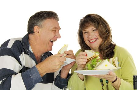 Middle aged couple laughing and enjoying lunch together.