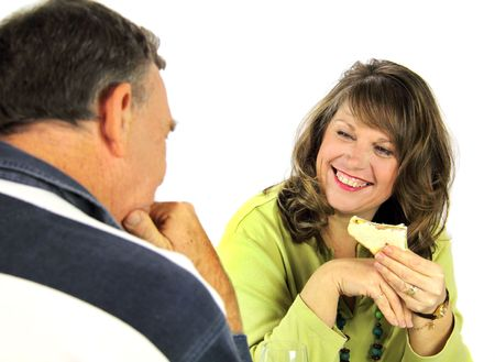 confab: Middle aged couple laughing and enjoying lunch together.