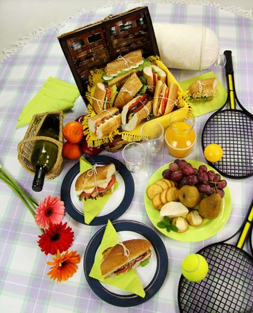 hamper: Selection of food for a picnic with a hamper, basket, fruit, wine and tennis racquets.