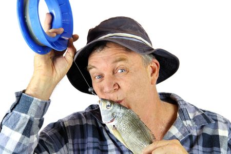 Middle aged fisherman kisses the fish he has just caught. Stock Photo - 5274918