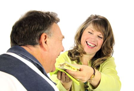 confab: Happy middle aged couple sharing a sandwich. Stock Photo