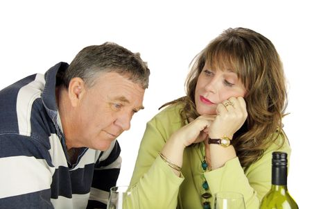 Dejected middle aged couple after having had an argument.
