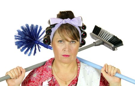tedious: Bored frumpy housewife with carpet sweeper and broom over her shoulders. Stock Photo