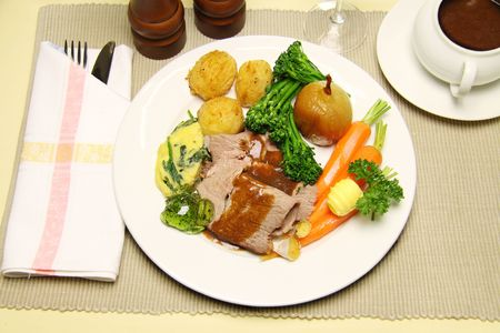 Delicious sliced roast lamb with baked vegetables and mint jelly. photo