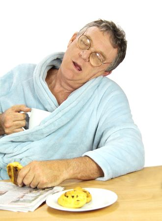 slumped: Nerdy middle aged man falls asleep at the breakfast table with a cup of tea and muffins.