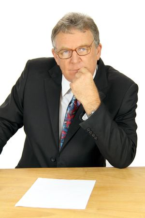 businessman pondering documents: Middle aged business executive ponders his next move. Stock Photo
