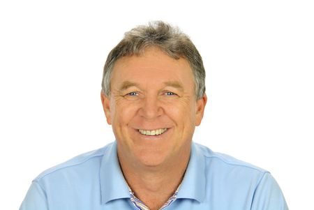 Close up of middle aged casual man smiling and sitting.