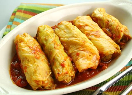 Piping hot baked cabbage rolls with a tomato sauce ready to serve.
