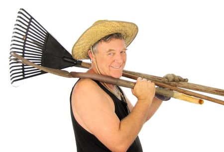 Middle aged gardener off to work with tools over his shoulder. photo