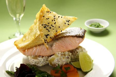 Delicious crispy skin salmon with fried wontons on a bed of mustard potatoes. photo