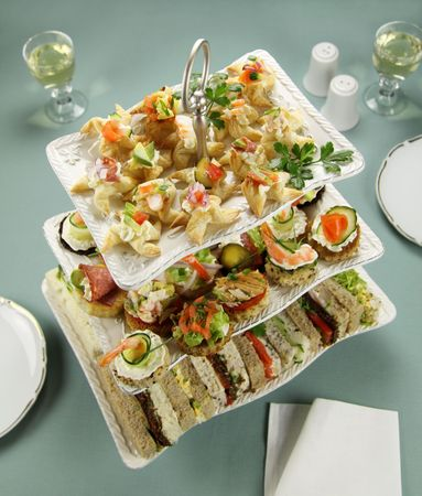 Delicious assorted finger food and sandwiches on a three tier stand. photo