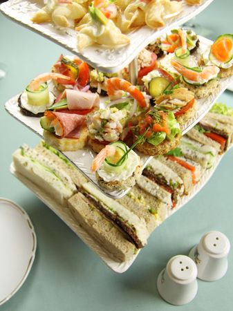 nibbles: Delicious assorted finger food and sandwiches on a three tier stand. Stock Photo