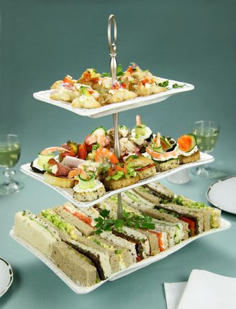 Delicious assorted finger food and sandwiches on a three tier stand. Stock Photo