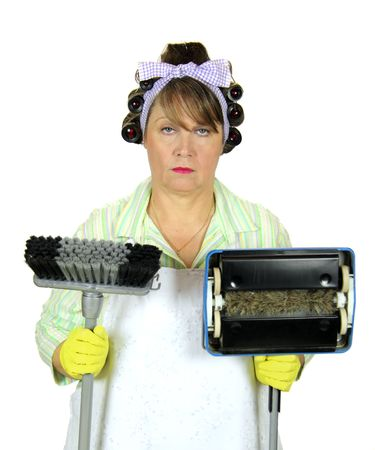 dreary: Unhappy and apathetic frumpy housewife standing with broom and carpet sweeper. Stock Photo