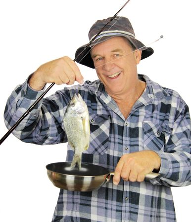 Middle aged fisherman drops freshly caught fish into fry pan. photo