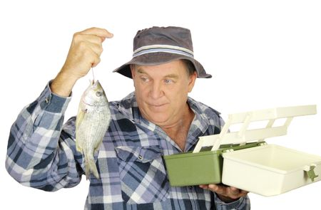 Middle aged fisherman holding freshly caught fish with open tackle box. photo