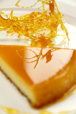 toffee: Stringy toffee reflected in the top of a slice of creme caramel dessert. Stockfoto