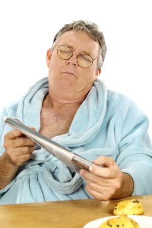 bath robe: Middle aged man in a bath robe struggles to read the morning paper.