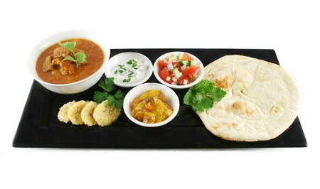 Indian feast of vindaloo curry, naan bread, mango chutney, banana and coconut, tomato and cucumber. Stock Photo