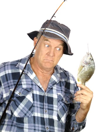 Middle aged fisherman is surprised by the size of his catch.