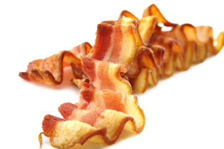 Strips of curly crispy bacon which have been baked.