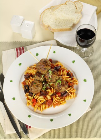 Delicious beef meatballs on tomato and olive pasta with bread and wine. photo
