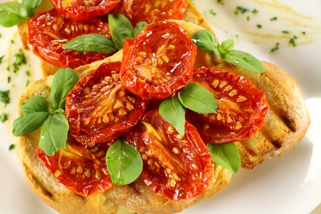 Delicious roasted cherry tomatoes with basil on bruschetta. photo