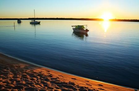 Sun streams over small boats in a still lagoon at dawn. Stock Photo - 7224580