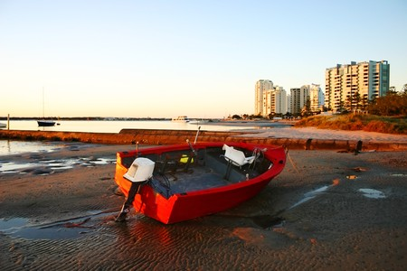 inlet bay: Battered old red dinghy with outboard motor lies on the beach at dawn. Stock Photo