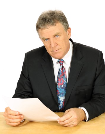 Resolute middle aged businessman with a steely glare sitting at desk. photo