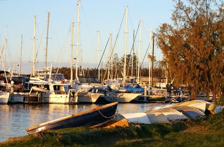 dinghies: Line of dinghies on the shore against marina boats at sunset. Stock Photo