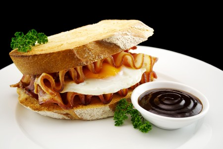 bbq sauce: Curled bacon and egg sandwich with BBQ sauce ready to serve.